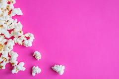Bakgrund med ett popcorn Rosa bakgrund med popcorn Lekmanna- lägenhet, bästa sikt arkivfoton
