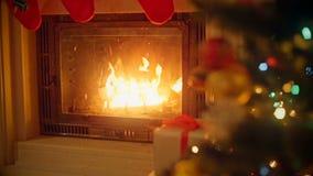Bakgrund med färgrika struntsaker på julgranen bredvid den brinnande spisen på vardagsrum lager videofilmer