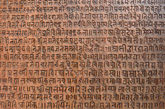 Bakgrund med forntida sanskrit text etsade in i en minnestavla Arkivbilder
