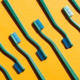 Bakgrund med gröna tandborstar, på guling Royaltyfria Bilder