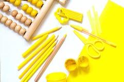 Bakgrund med gul plasticine, färgade blyertspennor och annan för Royaltyfria Bilder