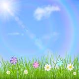 Bakgrund med himmel, solen, moln, regnbågen, gräs och blommor Fotografering för Bildbyråer
