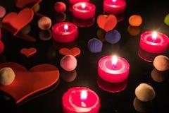 Bakgrund med hjärtor, stearinljus och färgade bollar Förälskelse färg royaltyfri foto