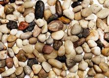 Bakgrund med många olika kulöra stenar Arkivfoton