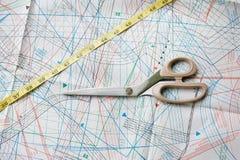 Bakgrund med modellen och att mäta bandet och scisso Arkivbild