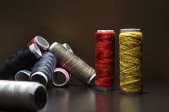 Bakgrund med mycket färgrika spolar med trådar Spolar staplas i tre rader, en på annan Spolningen är oregelbunden arkivfoto