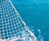 Bakgrund med nätverk från yachtsegelbåten i det blåa havet royaltyfri fotografi