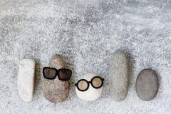 Bakgrund med olika roliga tecken av stenar på grå färgerna t Arkivbild