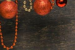 Bakgrund med röda bollar och pärlor mot mörk träyttersida royaltyfria bilder