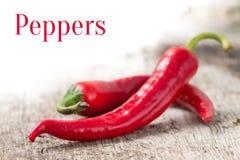 Bakgrund med röda peppar och tömmer utrymme Royaltyfri Foto