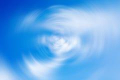 Bakgrund med radiell suddighetseffekt för snurrande av blå molnig himmel Royaltyfria Foton