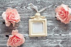Bakgrund med rosa rosor och ram med en ängel på grå färgerna b royaltyfria bilder