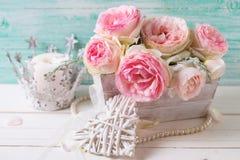 Bakgrund med söta rosa rosor blommar i träasken, decorat arkivbild