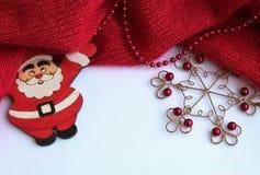 Bakgrund med Santa Claus och en härlig metallsnöflinga witRed stuckit, stuckit stramt på en ljus bakgrund med röda pärlor royaltyfria bilder