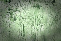Bakgrund med sprucken grön målarfärg och karaktärsteckning Textur av den gamla grova beläggningen En vägg med en ovanlig abstrakt Arkivfoto