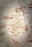 Bakgrund med sprucken vit och röd målarfärg Textur av den gamla grova beläggningen En vägg med en ovanlig, abstrakt begreppmodell Arkivfoto