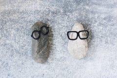 Bakgrund med två roliga tecken av stenar på den gråa surfaen Fotografering för Bildbyråer