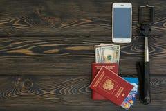 bakgrund mer mitt portföljlopp Olik saker som du behöver för resan - smartphone, pass, selfiepinne, pengar, kreditkort placera te Royaltyfria Bilder