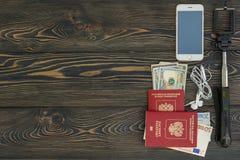 bakgrund mer mitt portföljlopp Olik saker som du behöver för resan - smartphone, pass, selfiepinne, pengar, kreditkort placera te Arkivbild