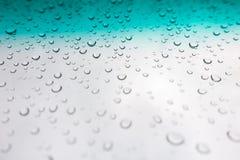 bakgrund tappar vatten Vatten tappar på det glass fönstret över blått sk Royaltyfri Foto
