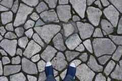 Bakgrund textur av den grova stenen på trottoaren Benen i gymnastikskorna är en bästa sikt Arkivfoto