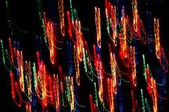 Bakgrund, textur, ljus abstrakt modell i olika linjer för en färg, band och fläckar på en svart bakgrund, neon Royaltyfri Foto