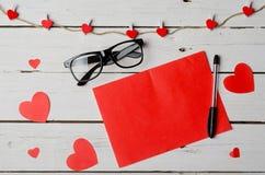 Bakgrund till dagen av valentin: hjärtor, papper, penna och exponeringsglas Arkivbild