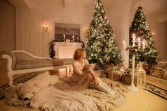 bakgrund undersöker år för toys för mörk afton nytt s för julsammansättning Ung härlig blond kvinna med kopp kaffesammanträde i k Royaltyfri Foto