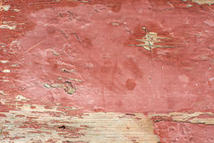 Bakgrunden av ett gammalt träbräde målas med röd målarfärg, som klättrade arkivbild