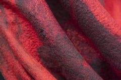 Bakgrunden av filten draperar är svart rött royaltyfri bild