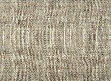 Bakgrunden av texturerat beige naturligt tyg arkivfoton