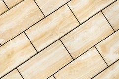 Bakgrunden göras med beigea tegelplattor som diagonalt förläggas Arkivfoton