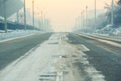 Bakgrunden, väg på en tom gata i stad, kall vinterdag med snö och agens på skymning, flyg- perspektiv Arkivbild