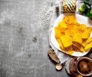 bakgrundsöl innehåller lutningingreppet Öl och chiper på stenbakgrund royaltyfri fotografi
