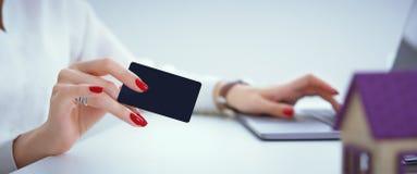bakgrundsbegreppsgodset investerar isolerad verklig white kvinnan gör en betalning med en kreditkort för köpet av fastigheten på  Arkivfoton