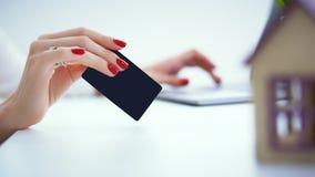 bakgrundsbegreppsgodset investerar isolerad verklig white kvinnan gör en betalning med en kreditkort för köpet av fastigheten på  Arkivbilder