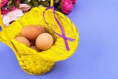 bakgrundsbröd bakar ihop white för skuggor för förberedelse för easter äggbakelser slapp Gul korg med fega ägg på violett bakgrun Arkivfoton