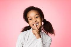 bakgrundscovering henne barn för kvinna för studio för tystnad för for för keepmunshhhh vitt Finger för afrikansk amerikanflickai arkivfoto