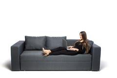 bakgrundsdatorutgångspunkten isolerade working för kvinna för sofa för bärbar dator liggande vit bakgrund isolerad white Arkivfoto