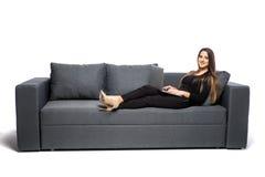 bakgrundsdatorutgångspunkten isolerade working för kvinna för sofa för bärbar dator liggande vit bakgrund isolerad white Arkivbild