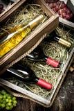 bakgrundsexponeringsglasrött vin Flaskor av rött och vitt vin i gamla askar royaltyfria bilder