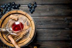 bakgrundsexponeringsglasrött vin Trumma med rött vin och druvor royaltyfri foto