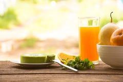 Bakgrundsfrukt i bunke och fruktsaft med kakan och mintkaramellen för grönt te På sikt och ferie för träbakgrund utomhus- med kop Arkivfoto