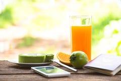 Bakgrundsfrukt och fruktsaft med kakan och mintkaramellen för grönt te med smartphonen och passet All skärm för lopp royaltyfri fotografi