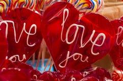 bakgrundsgodisen isolerade lollypop över röd enkel textwhite älskar jag dig lollyen med den snabba banan Royaltyfri Foto