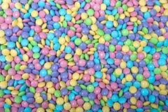 Bakgrundsgodisen täckte choklader i easter färger arkivfoton