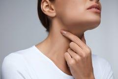 bakgrundshand som isoleras över för halswhite för ställe sjuk öm kvinna Kvinnahänder och hals för Closeup härliga Halsen smärtar royaltyfria foton