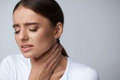 bakgrundshand som isoleras över för halswhite för ställe sjuk öm kvinna Sjukt kvinnalidande från smärtar, smärtsamt svälja Arkivfoton