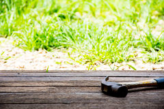 Bakgrundshantverkarehjälpmedel med den gamla hammaren på träbakgrund och utomhus- siktslandsstil Royaltyfri Bild