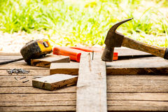 Bakgrundshantverkarehjälpmedlet liksom den gamla hammaren med måttband och litet spikar och såg med handsken och utomhus- sikt Ba Arkivfoto